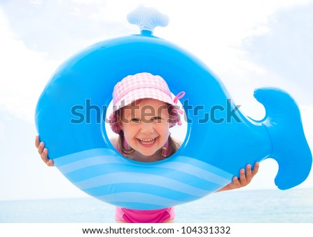 little girl in swimsuit playing with an inflatable whale on the beach - stock photo