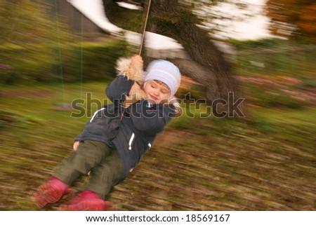 Little girl in swings, blurred motion - stock photo