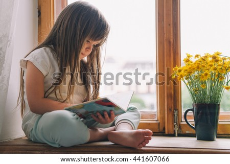 little girl in the bedroom. little girl is considering a book. cute little girl sitting on a window and reading a book. Girl with a book. flowers on the window. - stock photo