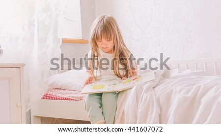 little girl in the bedroom. little girl is considering a book. pretty little girl sitting in the bed and reading a book. Girl with a book. - stock photo