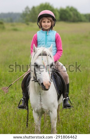 Little girl in the clothes for riding a horse sitting Sharpness on a horse  Outdoors - stock photo