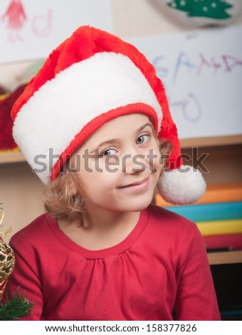little girl in the hat of Santa Claus - stock photo