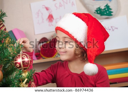 little girl in the hat of Santa Claus decorates a Christmas tree