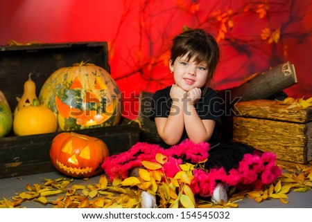 little girl in the image of a witch on Halloween with pumpkins and broom