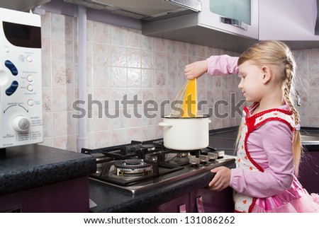 little girl in the kitchen putting pasta in the pot - stock photo