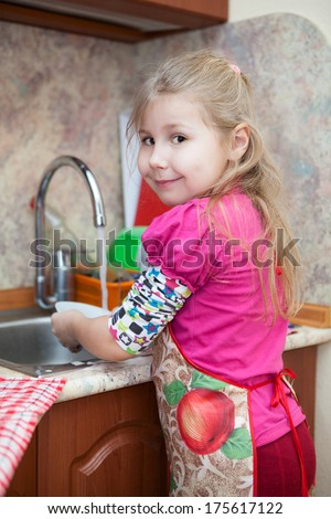 Little girl in the kitchen washing dishes - stock photo