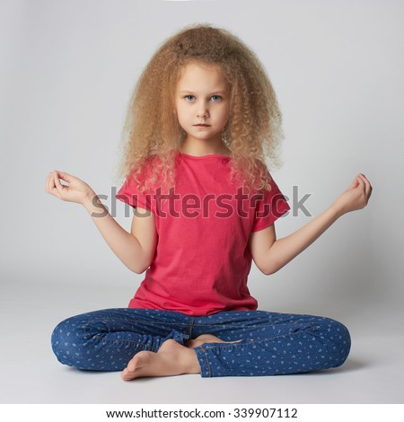 little girl in the lotus position.child does yoga.meditation and relaxation for health - stock photo