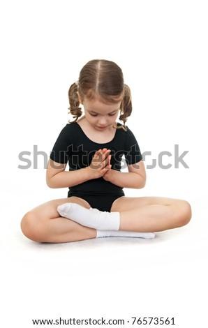 Little girl in the lotus position. Children's yoga. - stock photo