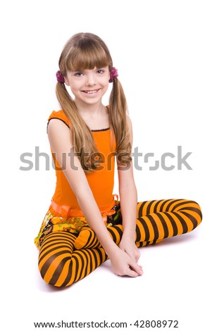 Little girl in the orange dress is sitting on the floor. Portrait of an attractive young teenager is smiling in orange over white background. - stock photo