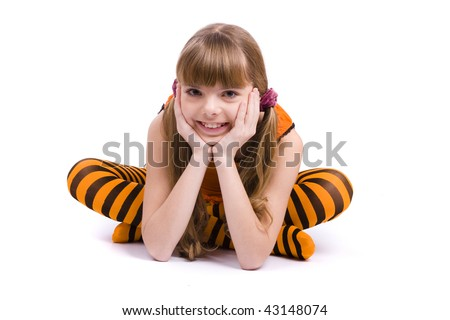 Little girl in the orange dress is sitting on the floor. Portrait of an attractive young teenager is smiling in orange over white background.