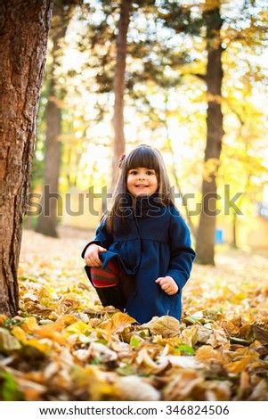 Little girl in the park Cute little girl playing in the park at autumn sunny day. She is looking at camera and smiling - stock photo