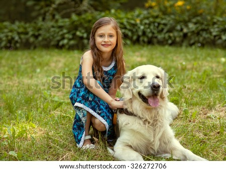little girl in the park their home with a dog