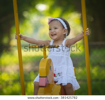 little girl in the park with playground - stock photo
