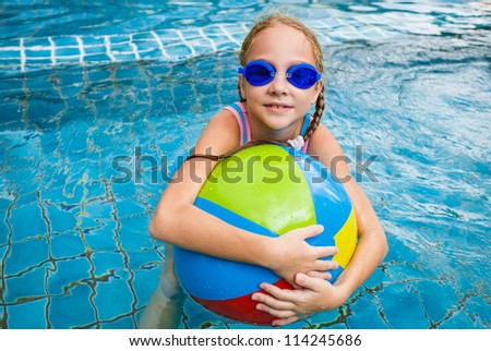 little girl in the pool with ball