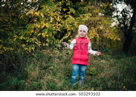 little girl in the red in the autumn forest, park