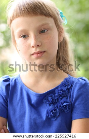 Little girl in the summer park, in a blue dress. blonde