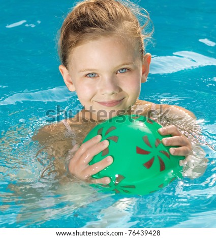 little girl in the swimming pool with ball - stock photo