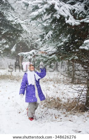 Little girl in the winter forest - stock photo