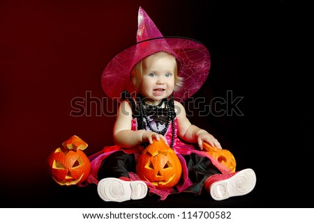 little girl in the witch costume with halloween pumpkin - stock photo
