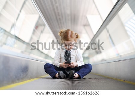 Little girl in tie with black mobile phone sits on travelator in gallery. - stock photo