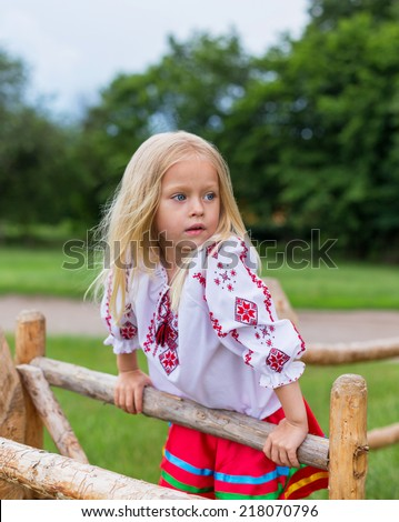 Little girl in ukrainian traditional clothes on the hedge in village - stock photo