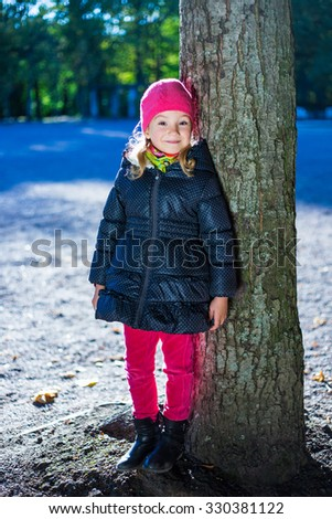 little girl in warm clothes in autumn park
