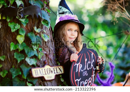 little girl in which costume celebrate Halloween outdoor and have a fun - stock photo