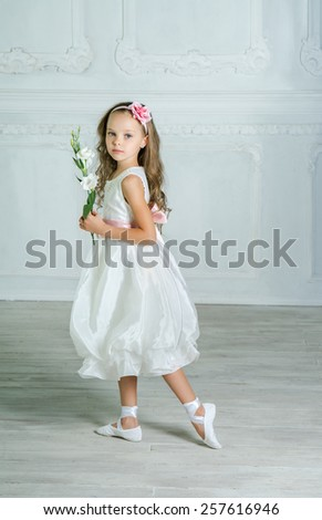 Little girl in white dress and flower is posing in a beautiful studio.