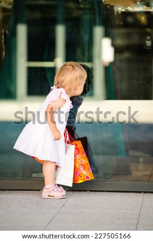 Little girl in white dress looking through shop window - stock photo