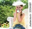little girl in wicker chair having tea party - stock photo