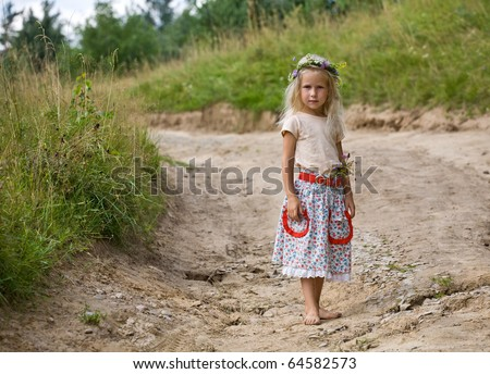 little girl in wild flowers wreath standing barefoot on summer road