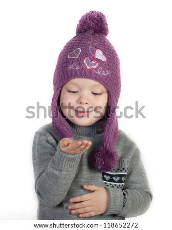Little girl in winter clothes with empty hand - stock photo