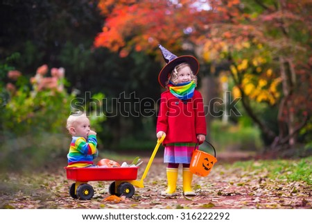 Little girl in witch costume and baby boy in wheel barrow holding a pumpkin playing in autumn park. Kids at Halloween trick or treat. Toddler with jack-o-lantern. Children with candy bucket in forest. - stock photo