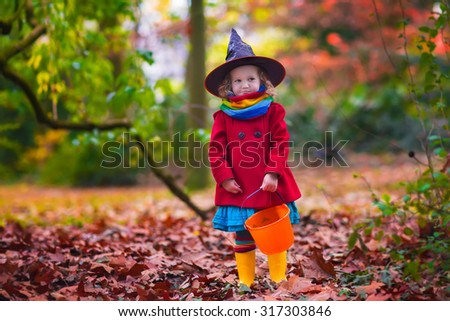 Little girl in witch costume playing in autumn park. Child having fun at Halloween trick or treat. Kids trick or treating.  Toddler kid with jack-o-lantern. Children with candy bucket in fall forest - stock photo