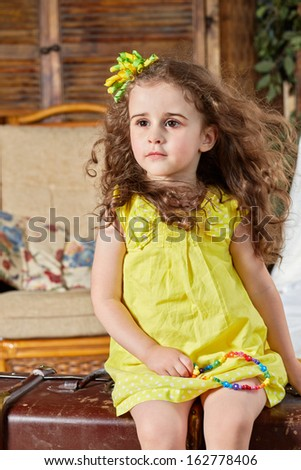 Little girl in yellow dress sits on old big ragged suitcase in room