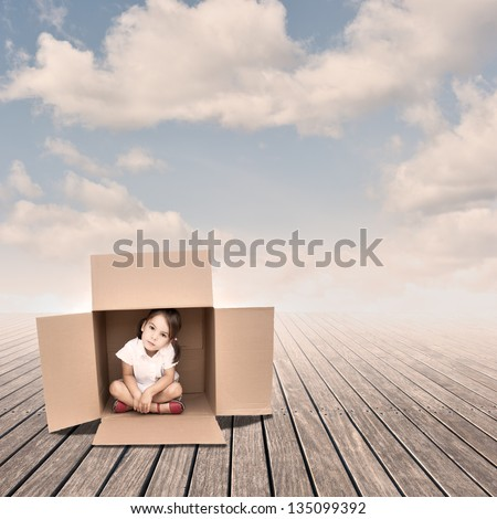 Little girl inside a Box on a pier - stock photo