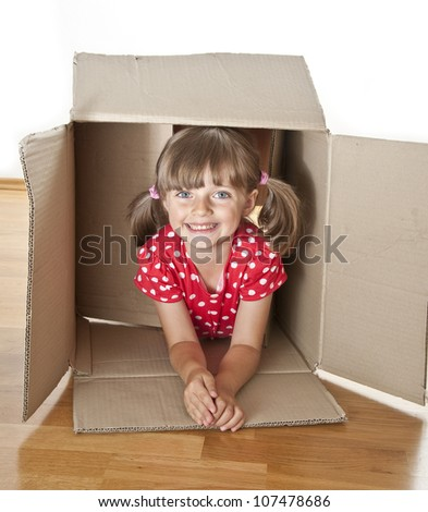 little girl inside a paper box - children play - stock photo