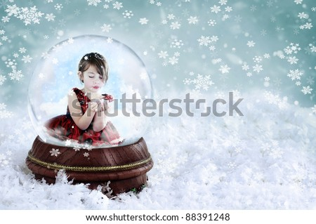 Little girl inside a snow globe blowing snow out of her hands. Copy space available. - stock photo