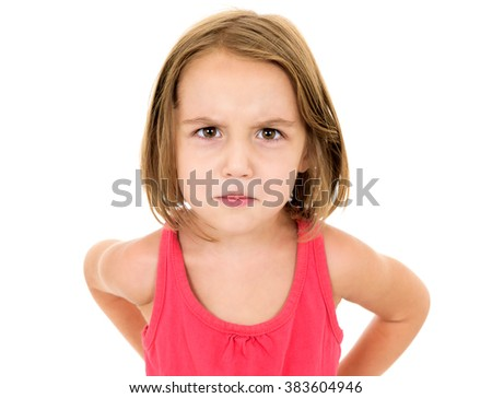 Little girl is angry, mad and looking at the camera. Emotion face. - stock photo