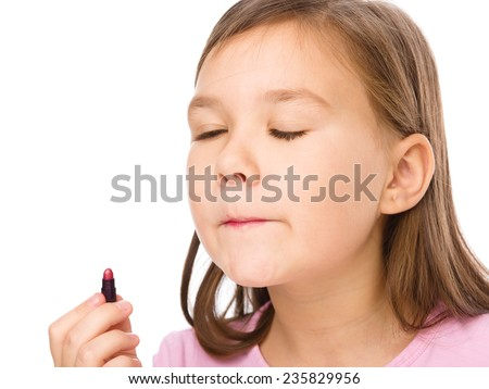 Little girl is applying lipstick, isolated over white - stock photo