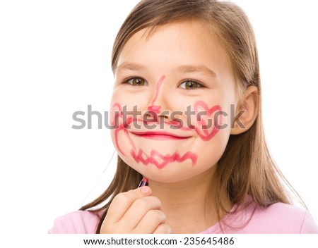 Little girl is applying lipstick on her cheek, nose and chin, isolated over white - stock photo