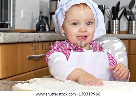 Little girl is baking in the kitchen - with many fun. She is looking to camera. - stock photo