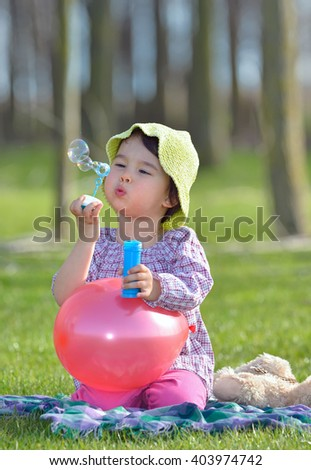 little girl is blowing a soap bubbles in forest - stock photo