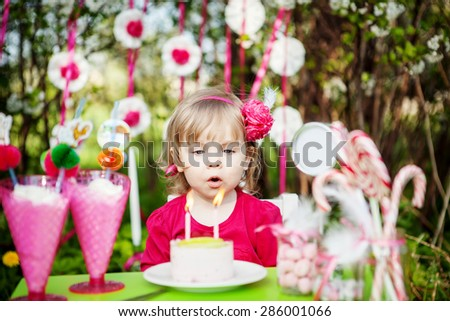 little girl is blowing birthday candles - stock photo