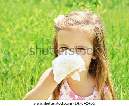 Little girl is blowing her nose on green meadow allergy - stock photo