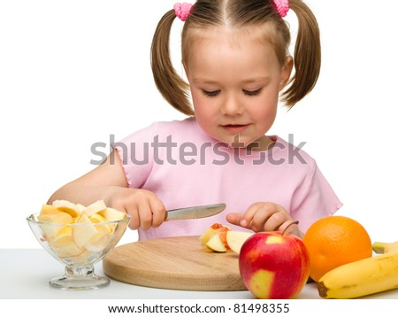 Little girl is cutting fruits for salad using kitchen knife, isolated over white - stock photo