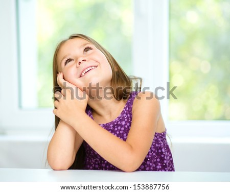 Little girl is daydreaming while sitting at table, isolated over white - stock photo