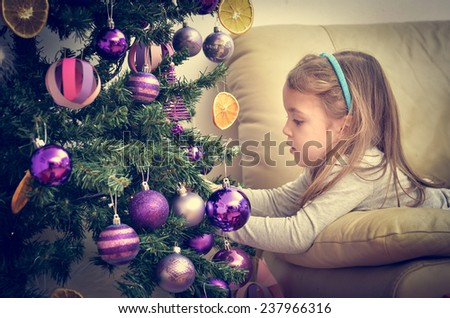 Little Girl is decorating Christmas Tree with home made Ornaments in retro filter effect or instagram filter - stock photo