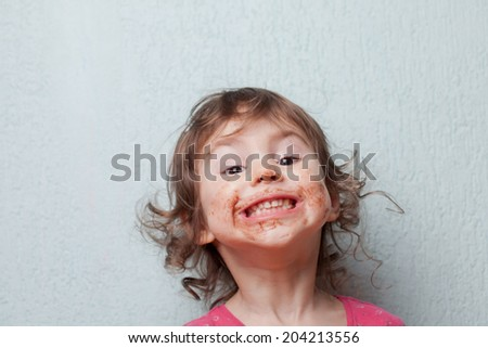 Little girl is dirty with chocolate. Funny face - stock photo