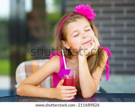 Little girl is drinking cherry juice using straw while sitting on terrace - stock photo